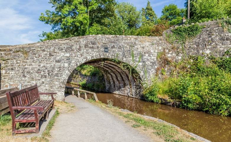 Canal, bridge and bench in Talybont-on Usk, Brecon, in Wales, UK. A good starting point for a walk along the famous canals o…