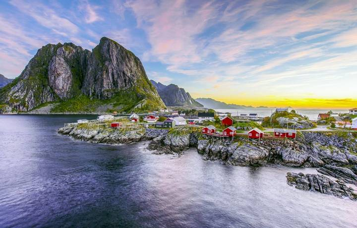 Popular view of Fishing hut (rorbuer) in Hamnoy, Norway with Lilandstinden mountain peak as the background during sunrise