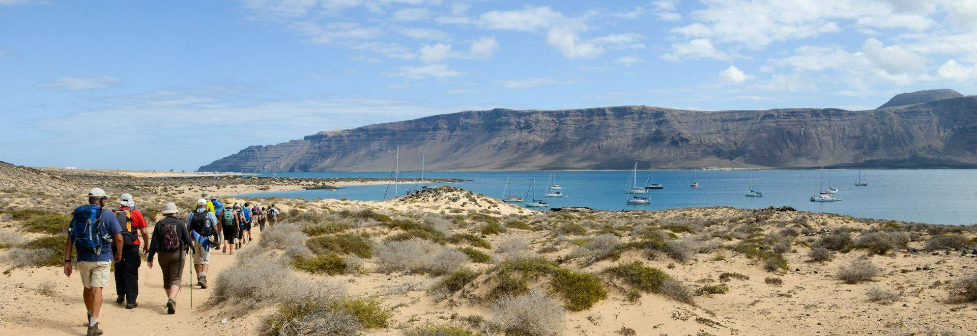 A group of tourists hinking on the sandy landscape of La Graciosa island (Canary islands, Spain), near Los Franceses beach. …