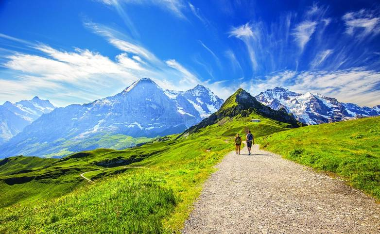 Young couple hiking in panorama trail leading to Kleine Scheidegg from Mannlichen with Eiger, Monch and Jungfrau mountain (S…