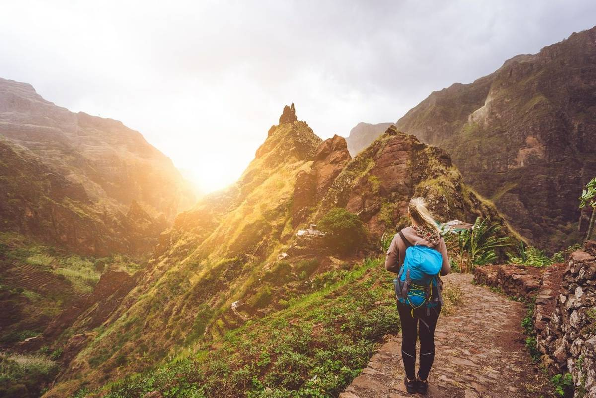 Girl walking down along the trekking route to verdant Xo-Xo valley. Warm sunlight seable on horizont. Santo Antao Island Cap…