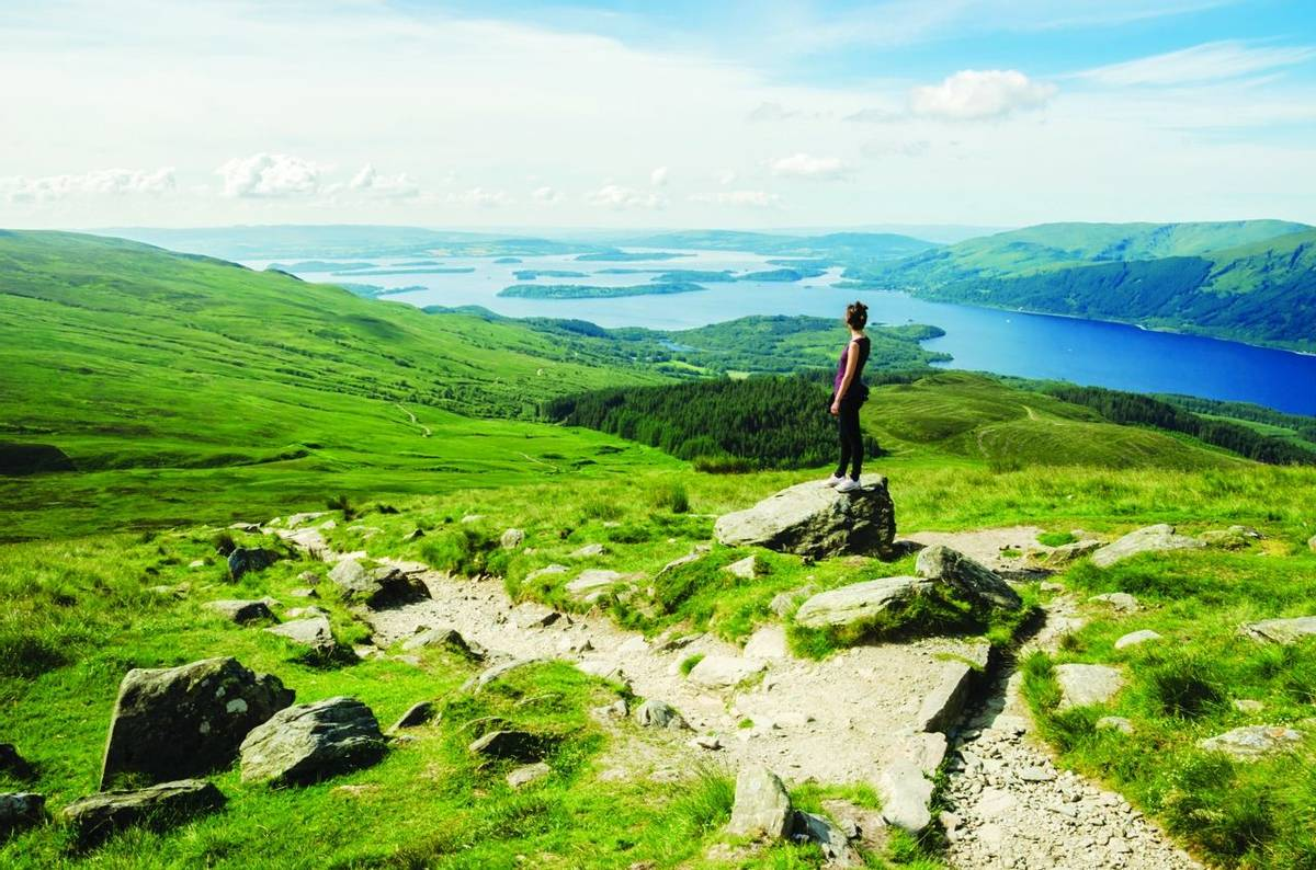 Female hiker admiring the landscape on a path leading to the top of Ben Lomond in a sunny  day. Loch Lomond in the backgroun…
