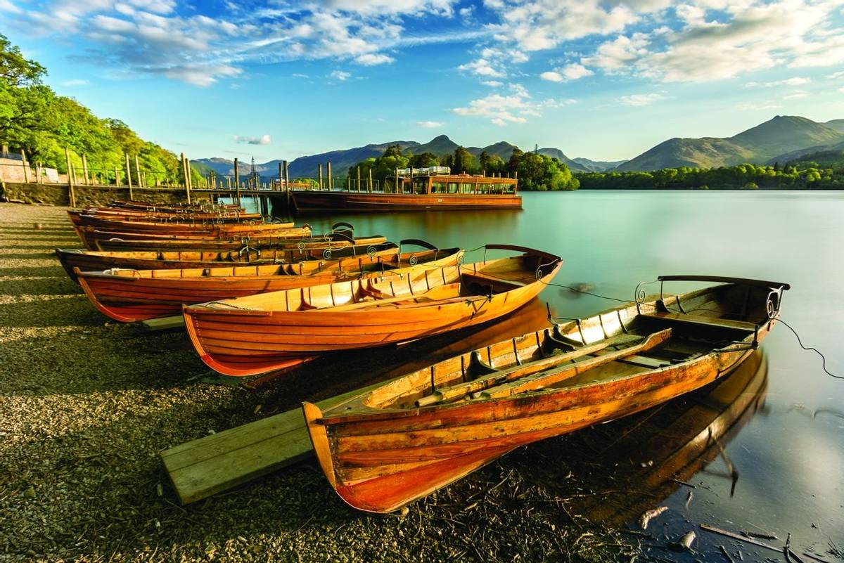 Wooden Rowing Boats lined up on shoreline being illuminated with golden light from the setting sun. Derwentwater, Lake Distr…