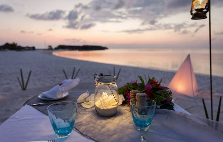 Romantic, private dinner setup at a tropical beach during sunset time
