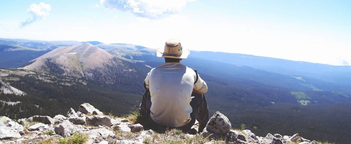 A man sat at the top of a mountain