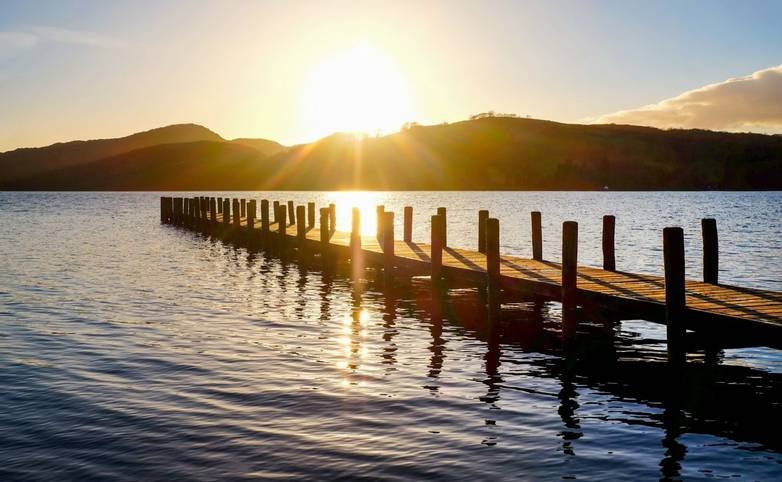 very long wooden jetty, jutting out into a calm blue wooden lake with mountains sunsetting in background
