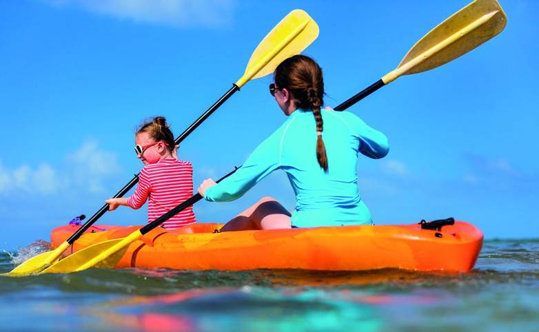 Family kayaking at tropical ocean
