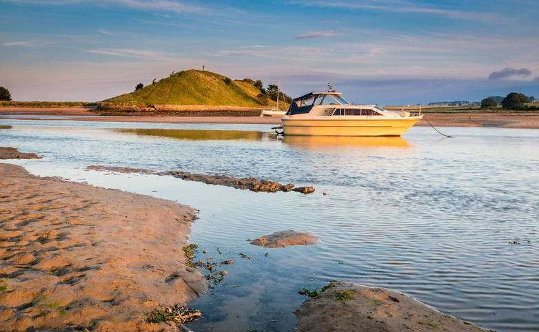 As the River Aln approaches the North Sea at Alnmouth, now tidal, there are several boats moored in the estuary