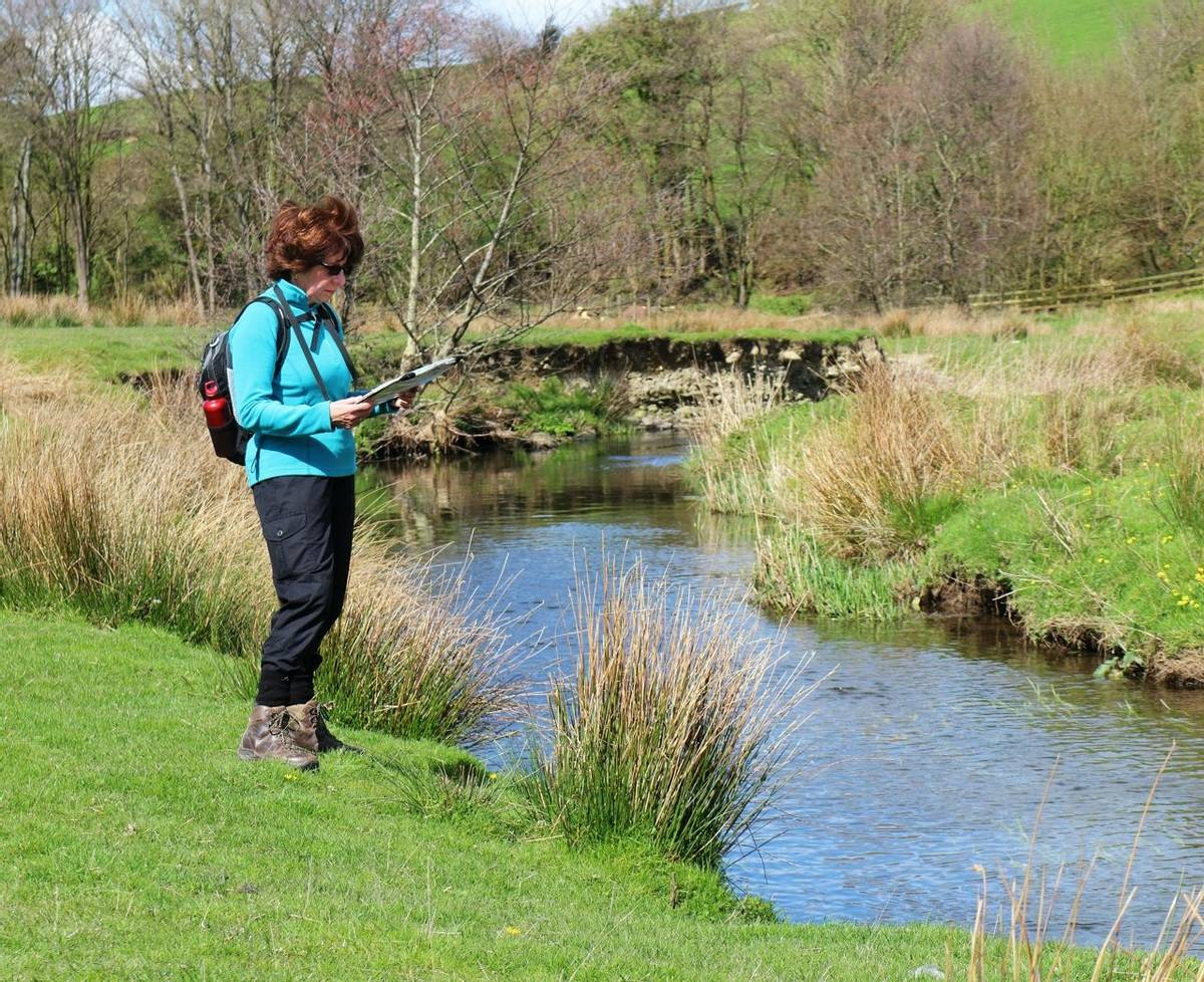Lady Rambler standing by a river in the Yorkshire Dales reading a map
