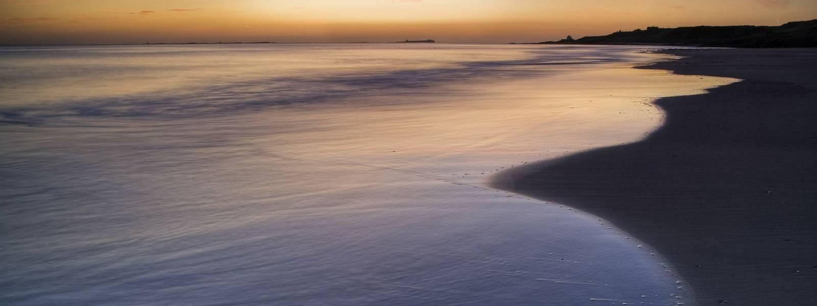 Pink pre-dawn light illuminates the sea at Budle Bay, Northumberland