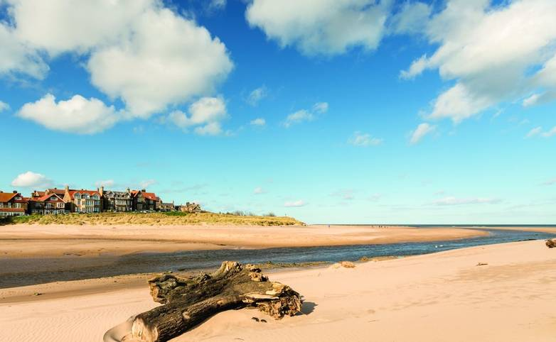 Alnmouth beach with driftwood as the River Aln meets the sea