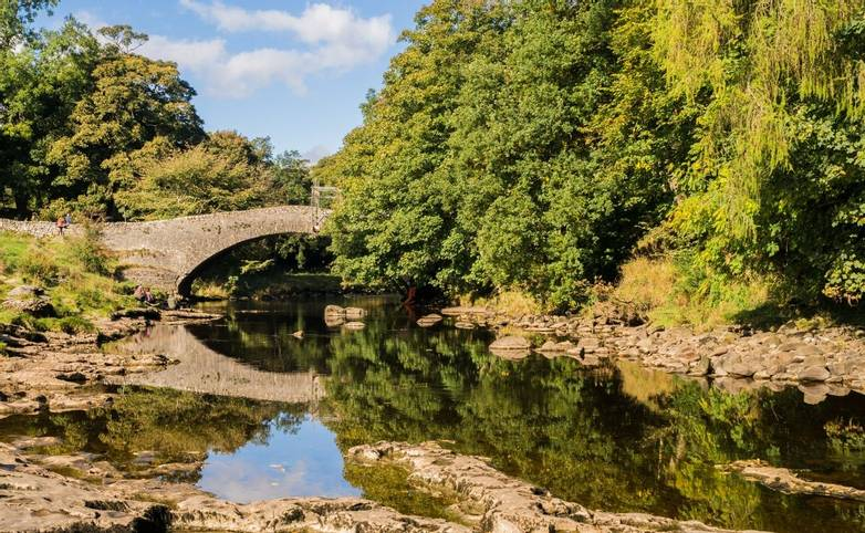 The river Ribble at Stainforth bridge in early Autumn sunshine, Stainforth, Settle, North Yorkshire, UK