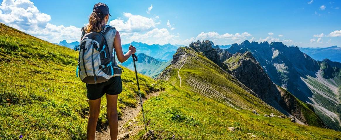 A hiker pauses to enjoy the view on a  mountain pass