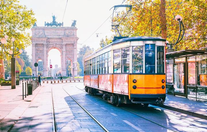 Famous vintage tram in the centre of the Old Town of Milan in the sunny day, Lombardia, Italy. Arch of Peace, or Arco della …