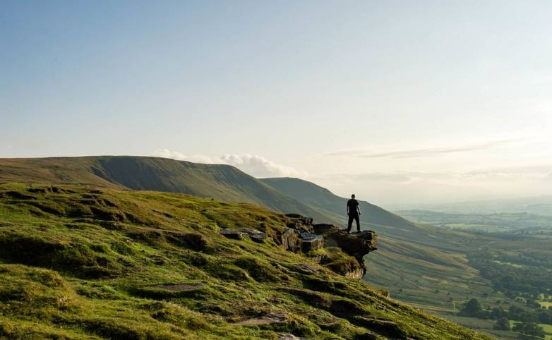 A man standing on the edge of a mountain, looking out across an escarpment, Black Mountains, Brecon Beacons, UK.