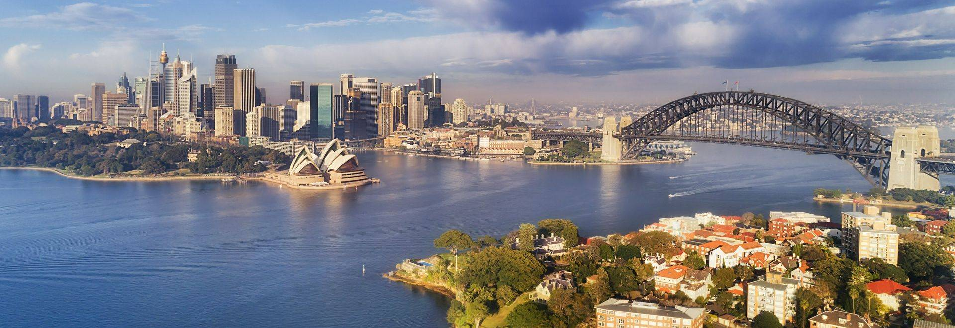 Quiet still earlier morning gentle sun light over Sydney city main landmarks around Harbour waters and shores between CBD an…