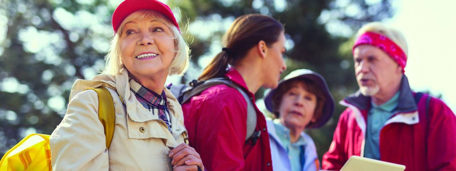 Nice spring day. Cheerful aged woman smiling while other hikers talking in the background