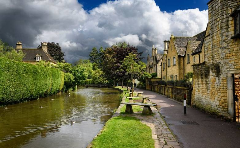 Ducks swimming on River Windrush in sunshine after a rain storm in Bourton-on-the-water Cotswold England