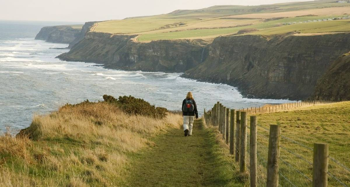 Walker on the coastal path, the Cleveland way in North Yorkshire, England, UK.
