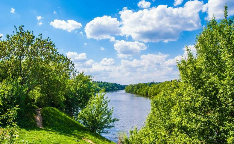 River lune landscape. Lane on the hill, green trees and clouds in blue sky.