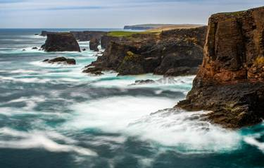 The wild Atlantic Ocean crashes against the sea stacks, rocks, and cliffs along the Western shore of Shetland Islands at Esh…