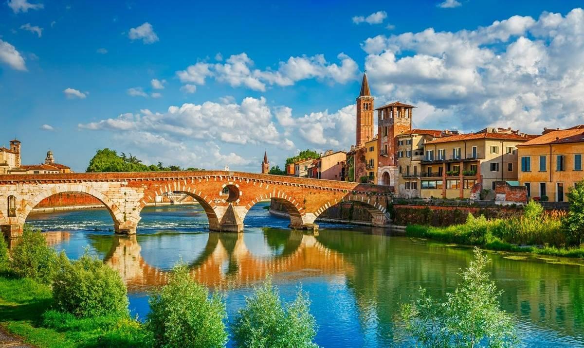 Panoramic view to Bridge Ponte Pietra in Verona on Adige river, Veneto region, Italy. Sunny summer day panorama and blue dra…