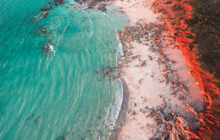 An aerial view of Gantheaume Point in Broome, Western Australia at golden hour just before sunset, with the sun lighting the…