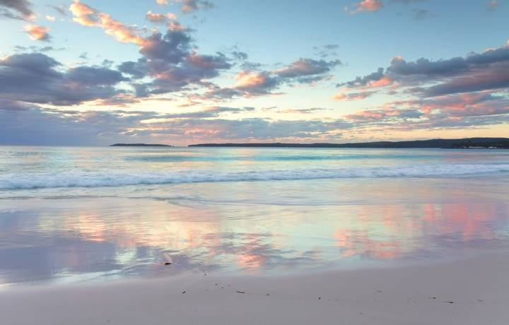 The pretty pastel colours of dawn sunrise and reflections in the water at Hyams Beach South Coast of NSW Austalia.  A wonder…