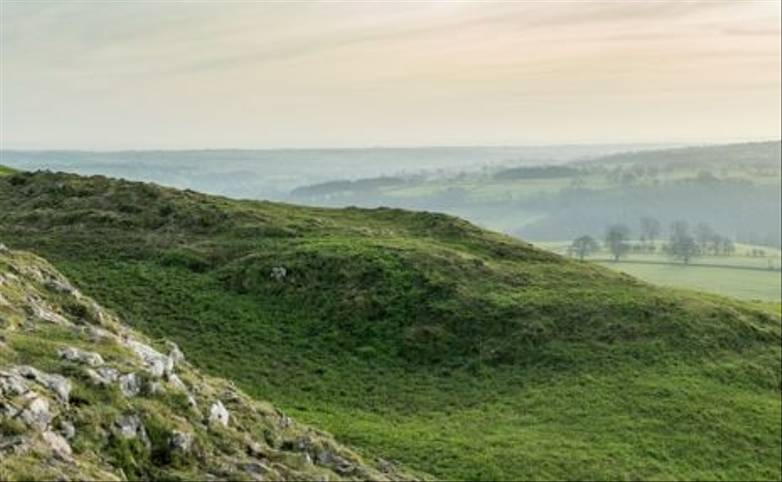 Panoramic view of the summit of Thorpe Cloud with hikers enjoying scenery, Peak District, Derbyshire.