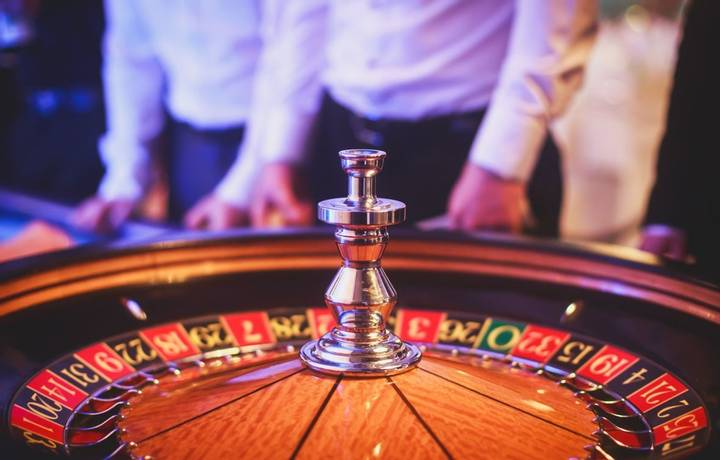 A close-up vibrant image of multicolored casino table with roulette in motion, with the hand of croupier, and a group of gam…