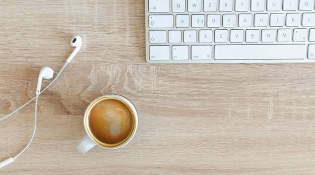 Computer keyboard with coffee and earphones