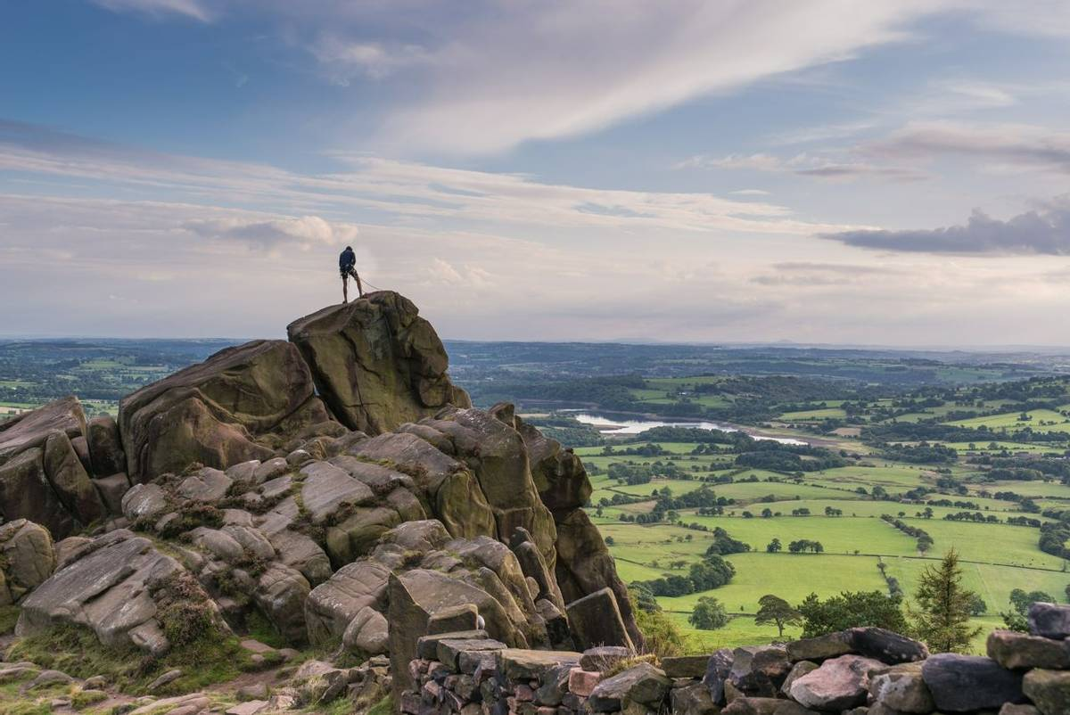 A climber at the roaches with a view over Tittisworth, Peak District National Park