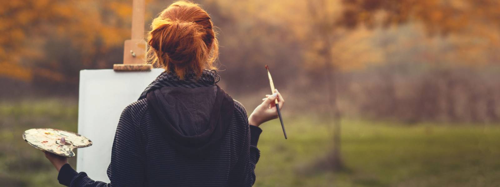 redhead girl drawing a picture on an easel in nature, young woman with a paint brush and a palette among autumn trees, a con…
