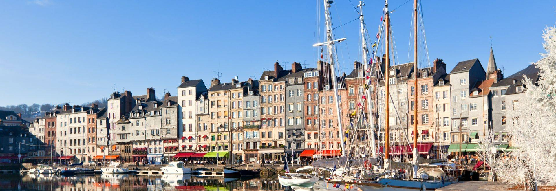 Honfleur harbour in Normandy, France. Color houses and their reflection in water.