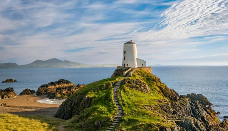 Llanddwyn island lighthouse with sea and Snowdonia mountains in background