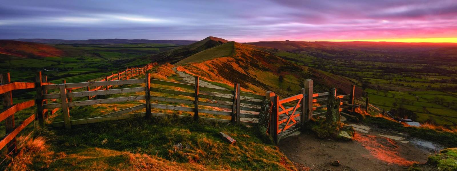 Glowing red light from the rising sun shining on countryside gate at Mam Tor in the Peak District with moody clouds.