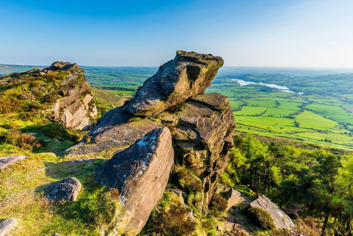 A overhanging rock and reservoir in the distance take the viewer into the Staffordshire moorland and beyond.