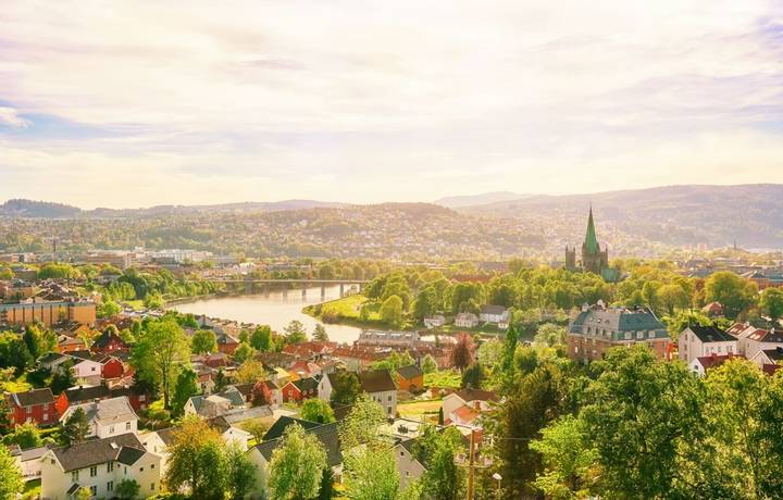 Aerial view of the river Nidelva, the Cathedral Nidarosdomen and historical center in the Norwegian city Trondheim at warm s…