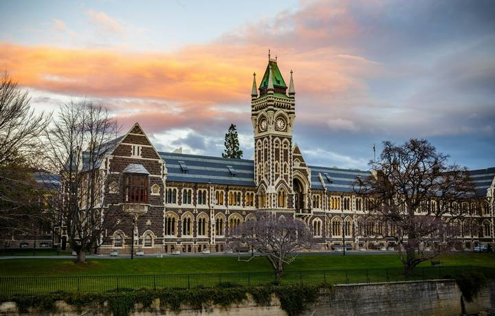 Old university campus building surrounded by winter trees under a vibrant multicoloured cloudy sky