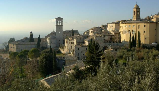 Tuscany (Italy) Looking down on a small Italian town - caught in late afternoon sunlight with a clear blue sky and distant p…