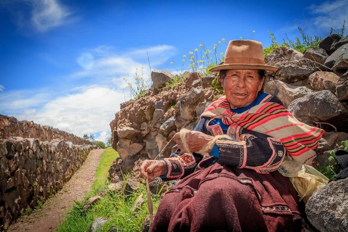 RAQCHI PERU -JANUARY 15: Unidentified Quechua indian woman knits handcrafts at Raqchi Ruins, Peru on January 15, 2013. Raqch…