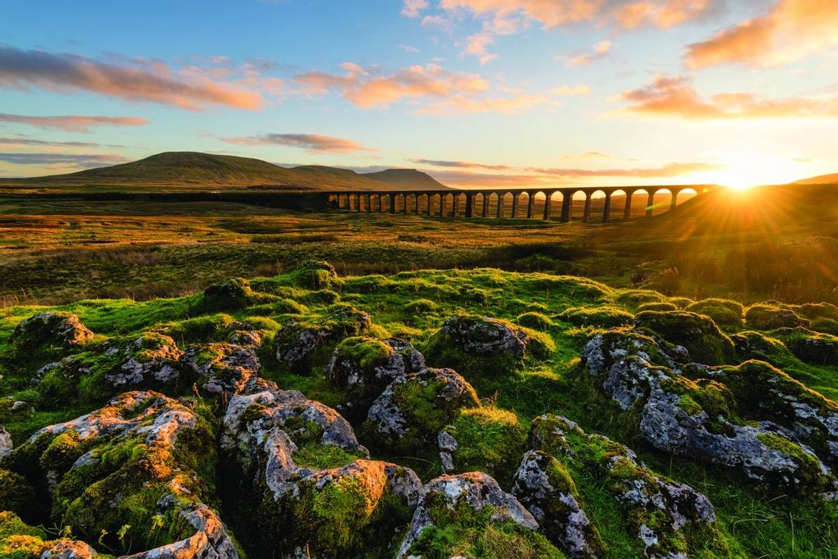 Gorgeous golden light as the sun sets behind the Ribblehead Viaduct with rocks in foreground.