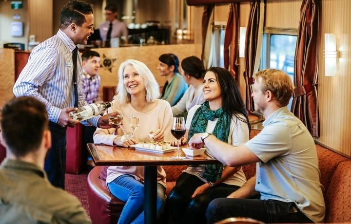JBRE-On train-outback lounge-HA serving group of people wine.jpg