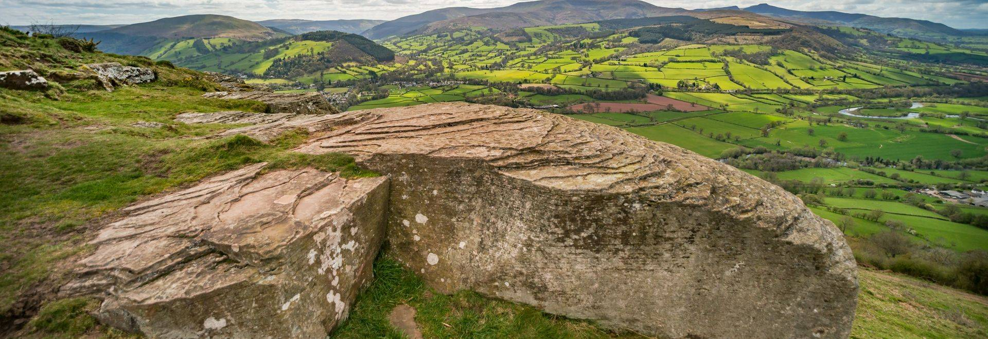 View over Usk valley to Brecon Beacons from Allt yr esgair hillside. Large rock with rippled pattern in foreground. Wales, U…