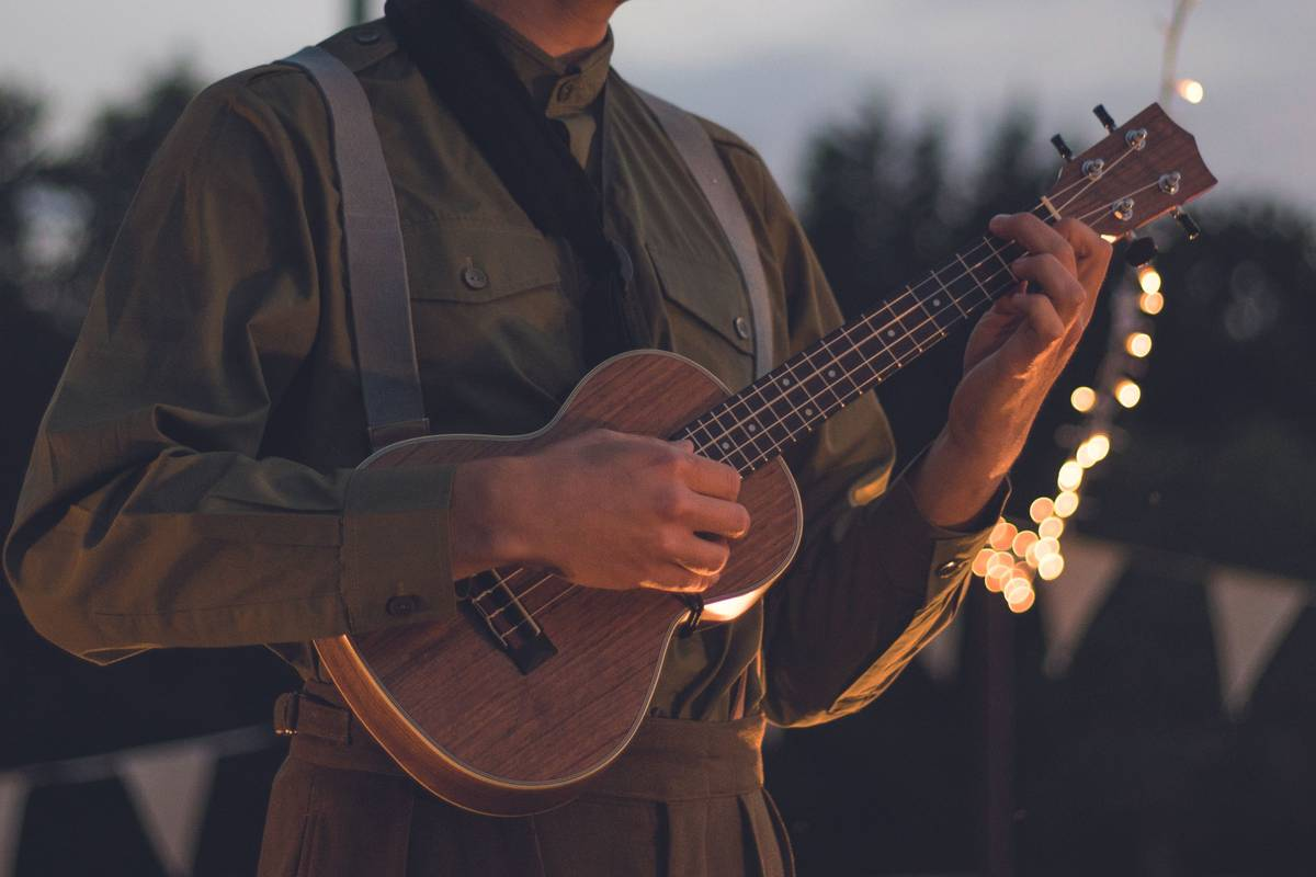 Man playing a ukulele outside on a summers evening