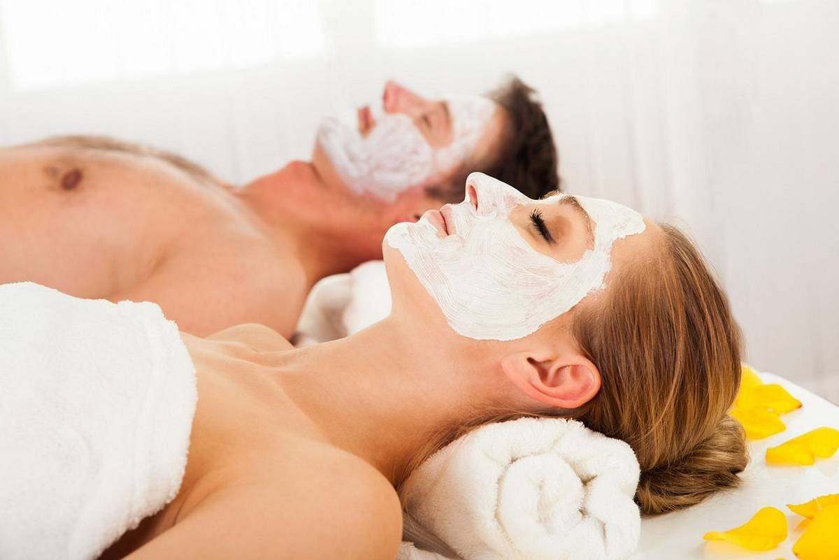 17260977 - man and woman in face masks lying back on clean white towels in a spa relaxing