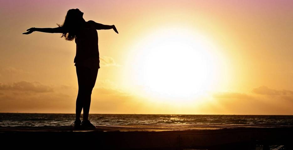Woman with outstretched arms in the sunset