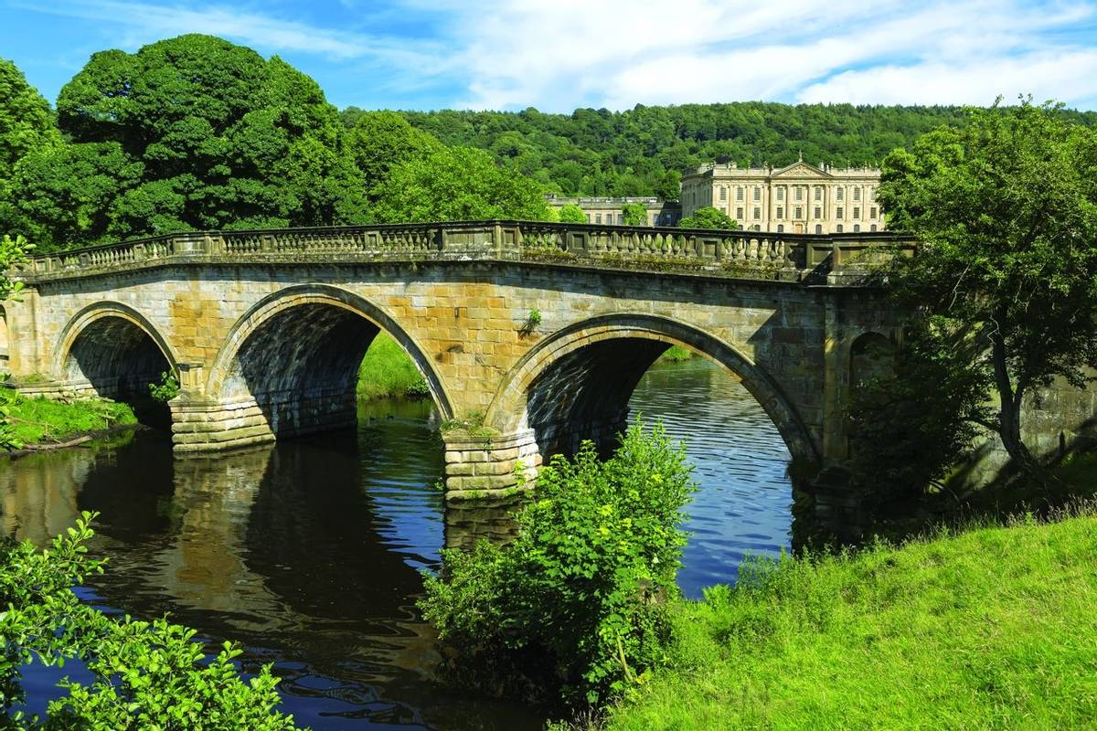 Stone road bridge over the River Derwent at Chatsworth house estate, Derbyshire.