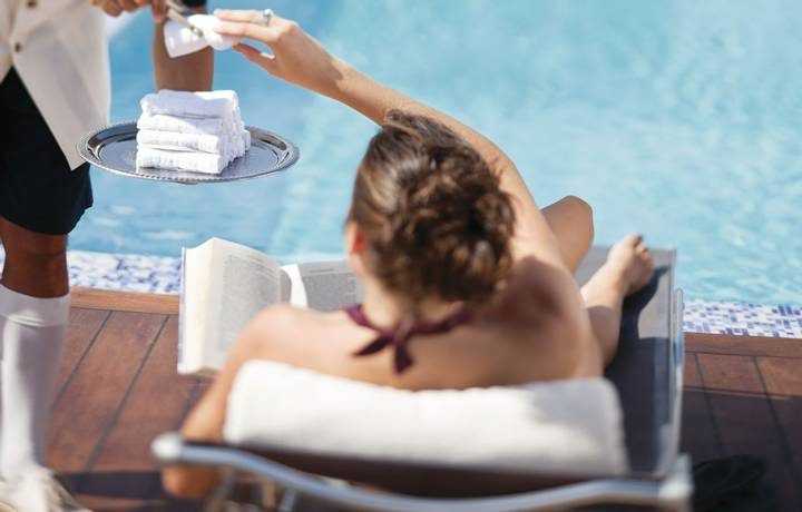 Waiter offers a towel to a guest on the pool deck, Silver Wind