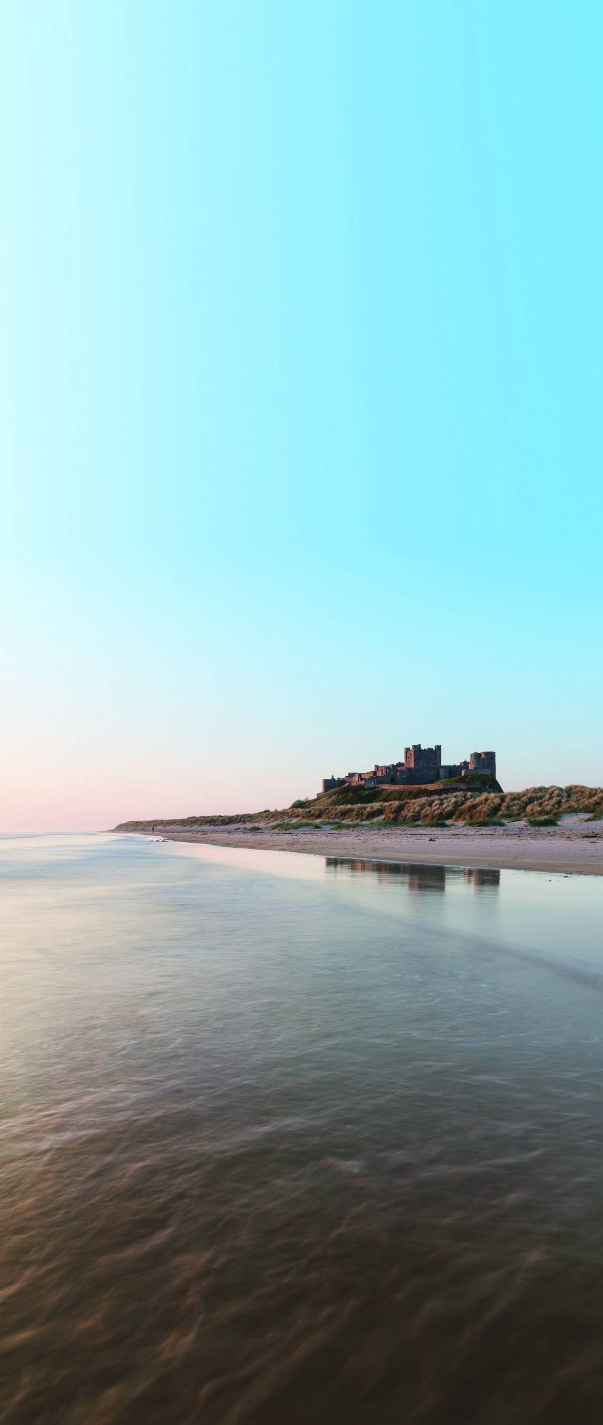 Beautiful landscape image of Bamburgh Castle on Northumberland coast at sunrise with vibrant colors